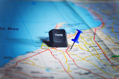 Home key with a push pin pinned on a map. Close up shot of map with a push pin beside a Home key taken from a keyboard. Map showing a location of someone stock photos