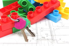 Home keys and building blocks on housing plan. Closeup of home keys and heap of colorful building blocks lying on construction drawing of house, building blocks royalty free stock photography