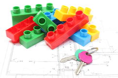 Home keys and colorful building blocks on housing plan. Closeup of home keys and heap of colorful building blocks lying on construction drawing of house Stock Photos