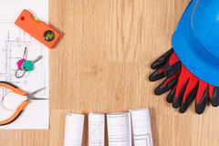 Home keys with electrical drawings, protective blue helmet with gloves and orange work tools, building home concept Royalty Free Stock Image