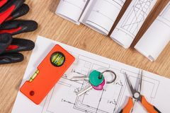 Home keys with electrical drawings, protective gloves and orange work tools, concept of building home. Home keys with blueprints or electrical construction Royalty Free Stock Photography