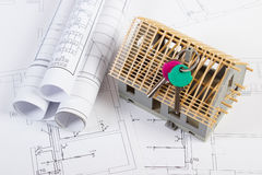 Home keys, small house under construction and electrical drawings, building home concept Royalty Free Stock Photography