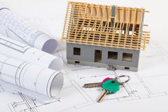 Home keys, small house under construction and electrical drawings, building home concept. Home keys, small house under construction and rolls of diagrams on stock photo