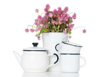 Home kitchen decor. Funny bouquet of pink wild flowers in a white vase, vintage enameled kettle and mugs isolated on white background Stock Image