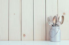 Home Kitchen Decor. Vintage cutlery, spoons and forks in zinc can on a wooden board background , cozy arrangement retro style, soft pastel colors Royalty Free Stock Images