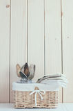 Home kitchen decor. Home decor: vintage wicker basket and cutlery on a wooden board background, cozy kitchen arrangement in retro style, soft pastel colors Stock Photos