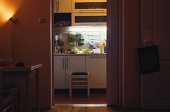 At home in the kitchen. A scene from ordinary life, a view from the living room to the kitchen, someone prepares food, it`s time for dinner Royalty Free Stock Photo