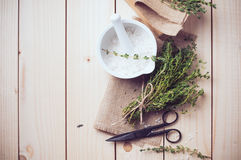 Home kitchen still life. Cozy rustic home kitchen still life, dried herbs thyme, salt in white mortar, old wooden box and vintage scissors on a table background Royalty Free Stock Image