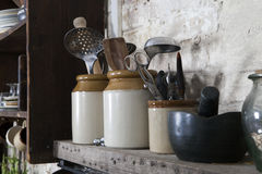 Home kitchen still life: Vintage coffee pot, enamel mugs and ant. Ique rustic wooden spoons on a barn wall background, soft pastel colors royalty free stock images