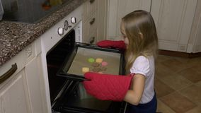 Home kitchen young girl in red mitts take tray with ginger cookies from oven. Hot biscuits from oven. Hand made meal stock video