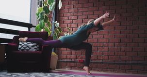 At home lady in living room practicing yoga for meditation she using a sofa to support the legs in this exercise.