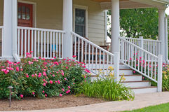 Home landscaping porch. Landscaping of front steps and porch to a country home with roses and day lilies as landscaping royalty free stock photo