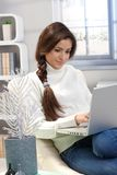 At home with laptop computer. Portrait of attractive woman sitting at home using laptop computer, winter ambience Royalty Free Stock Images