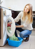 Home laundry. Happy blonde woman  the washing machine Royalty Free Stock Image
