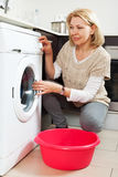 Home laundry. mature woman using washing machine Royalty Free Stock Photo