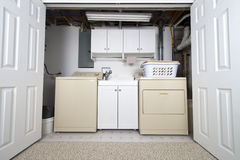 Home Laundry Room in Basement Closet and Utility Room. A home laundry room in a basement closet utility room. The appliances are used for washing clothes. You Royalty Free Stock Photography