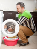 Home laundry. Smiling man looking clothes near washing machine royalty free stock images