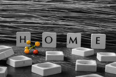 Home in Letters. Black and White Wooden square letters spelling the word `Home` outside next to red flowers on the concrete floor in the sunlight with colourful Royalty Free Stock Photo