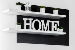 Home letters decor on white shelf. With dark wood background stock photography