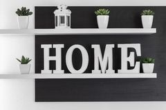 Home letters decor on white shelf. With dark wood background on white wall royalty free stock photography
