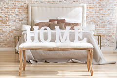 Home letters sign in interior near bed closeup. White wooden Home letters sign in interior near bed closeup stock photos