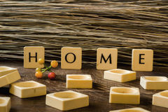 Home in Letters. Wooden square letters spelling the word `Home` outside next to red flowers on the concrete floor in the sunlight with colourful buildings in Royalty Free Stock Photo