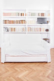 Home library with sofa or couch in white living room Royalty Free Stock Photo