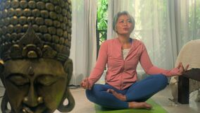 Home lifestyle - beautiful and happy mature woman with gray hair on her 50s doing yoga meditation exercise at Asian deco bedroom