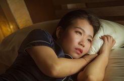 Home lifestyle portrait of young beautiful sad and depressed Asian Korean woman awake in bed late night suffering anxiety crisis royalty free stock image