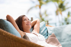 Home lifestyle woman relaxing enjoying luxury sofa. Patio furniture on outdoor patio living room. Happy lady lying down on comfortable pillows daydreaming Stock Photography