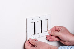 Home light switch faceplate removal Stock Images
