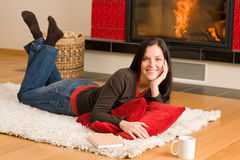 Home living happy woman lying by fireplace Royalty Free Stock Images