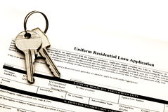 Home loan application. Uniform residential loan application document with two home keys - brown tone stock photos