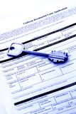 Home loan application. Uniform residential loan application document with a home key - blue tone stock photo