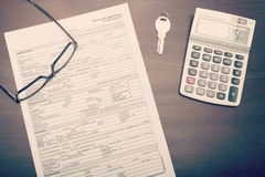 Home loan application form. On desk with glasses, key and calculator, viewed from abobve royalty free stock photo