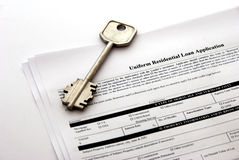 Home loan document. Uniform residential loan application document with a home key royalty free stock photos