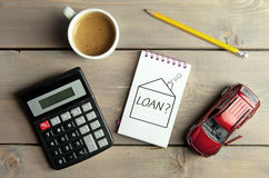 Home loan finances concept. Notepad with loan question inside a sketch of a house with a miniature car and calculator Royalty Free Stock Photo