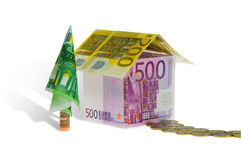 Home loan house made of money. A house with tree made of money. Conceptual image. Isolated on white background