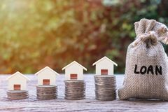 Home loan for house, real estate investment, financial wealth management concepts. House model on stack coins 4 step growing. Cash in hemp bags or burlap sacks royalty free stock photos