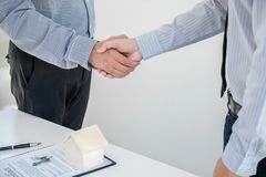 Home loan insurance concept, broker agent shaking hands with cus. Tomer after good deal agreement, home model Royalty Free Stock Photos