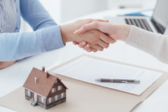 Home loan and insurance. Real estate broker and customer shaking hands after signing a contract: real estate, home loan and insurance concept