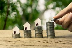 Home loan, mortgage, property investment, asset refinance concept. A man hand holding coin and a small house model on stack of coins. Depicts saving money for stock image