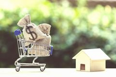 Home loan, mortgages, debt, savings money for home buying concept. US dollar money bag in shopping cart, residential, house on table against green nature royalty free stock photography