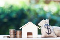 Home loan, mortgages, debt, savings money for home buying concept : US dollar in a money bag, small residential, house model on. Table against green nature stock photo