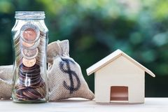 Home loan, mortgages, property investment, savings money concept. US dollar in a money bag and jar, small residential, house model on table with nature stock photos