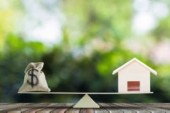 Home loan, home to money, Change real estate into cash concept. US Dollar in sack bag, Wooden house model on balance scales on wood table. Balance home and royalty free stock photos