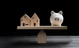 Free Home Loans Market. Model House And Piggy Bank Balancing On A Seesaw Royalty Free Stock Image - 183399706