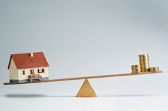 Home loans market. Model house and money coins balancing on a seesaw Stock Photo