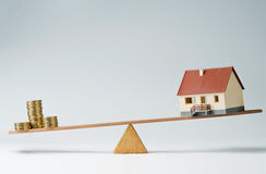 Home loans market. Model house and money coins balancing on a seesaw Royalty Free Stock Photography