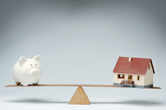 Home loans market. Model house and piggy bank balancing on a seesaw Stock Images